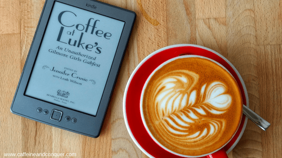 A latte sitting next to a Kindle with Coffee at Lukes displayed on the screen. Coffee At Lukes: An Unauthorized Gilmore Girls Gabfest.