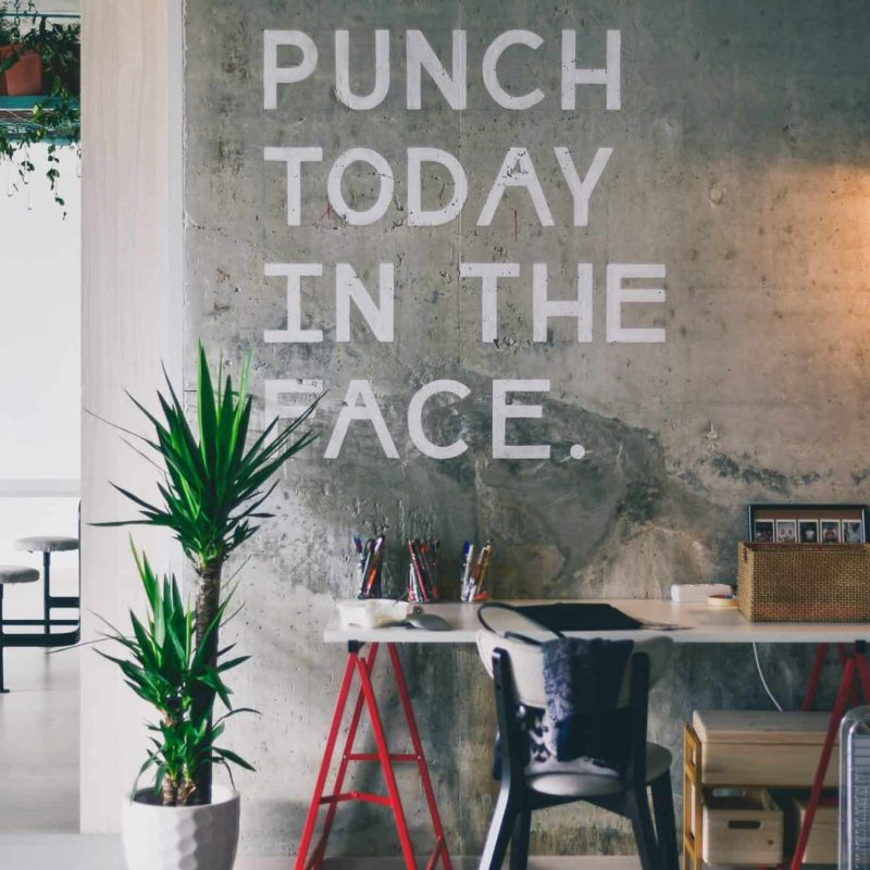 "A photograph of an office and desk. On the wall is graffiti'd ""Punch Today in the Face!"""