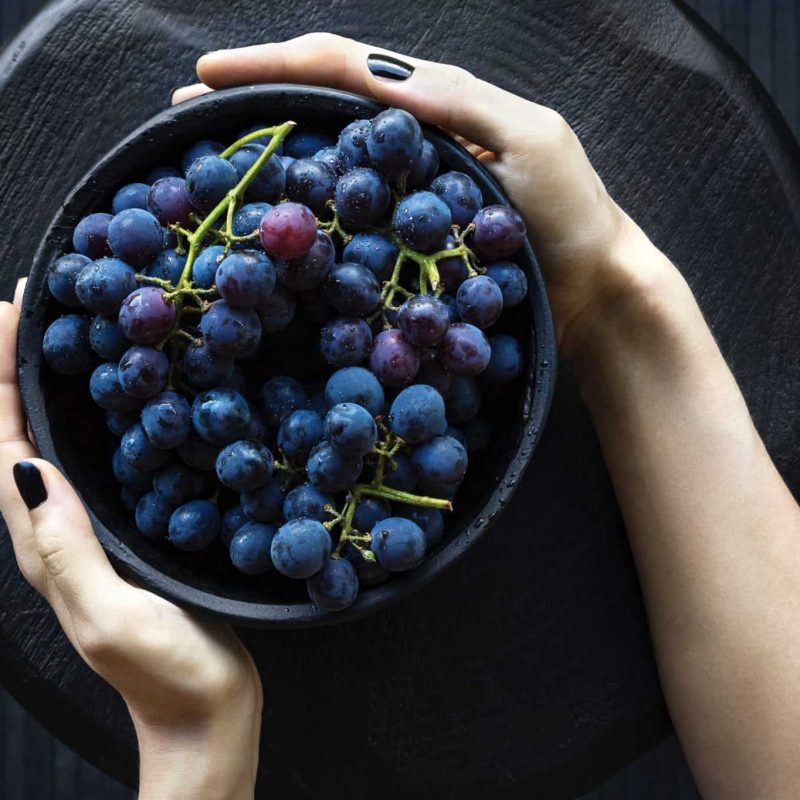 A flatlay photograph of a womens hands holding a bowl of dark grapes