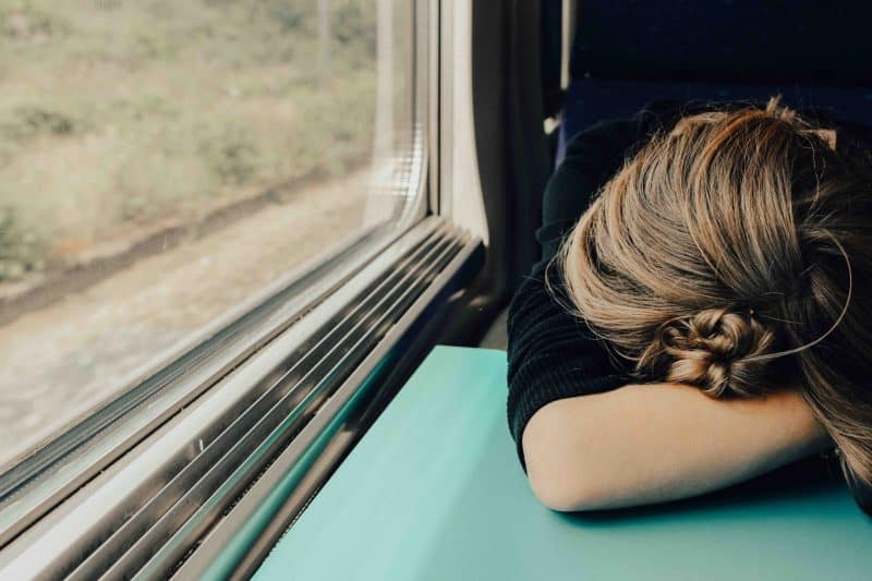 A woman on a train with her head down